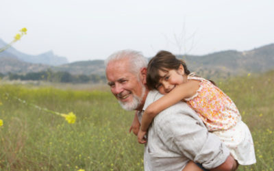 image of older man giving a little girl piggy back ride