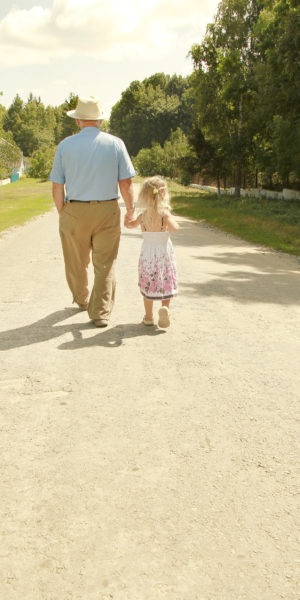 image of older man and young girl walking and holding hands